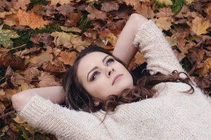 ragazza pensierosa sdraiata tra le foglie